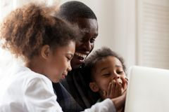 Happy African American family using laptop together at home. Happy African American family using laptop, computer together, father with daughter and preschooler royalty free stock photo