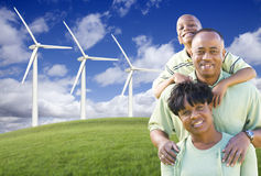Happy African American Family and Wind Turbine. With Dramatic Sky and Clouds Royalty Free Stock Images
