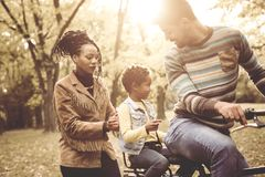 Happy African American Father driving daughter on bike. stock image