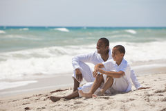 Happy African American Father and Son On Beach. A happy African American men and boy, father and son, family together on a tropical beach in summer sunshine
