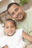 Happy African American Father and Son Family. A happy African American men and boy, father and son, family sitting together at home Stock Images
