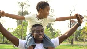 Happy African American father and son piggyback in outdoor park. Family weekend activity