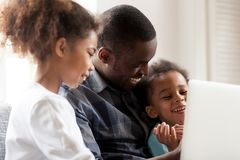 Happy African American young family watch cartoons on laptop. Happy African American father spend time with small kids, watch cartoons on laptop together royalty free stock images
