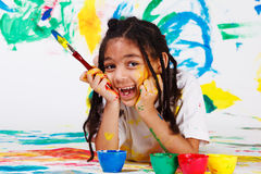 Happy african american girl. Lying on the floor with a paintbrush Royalty Free Stock Images
