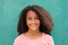 Happy African American girl with afro hair on a green background. Cute African American girl smiling with afro hair on a green background royalty free stock photography