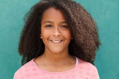 Happy African American girl with afro hair on a green background Stock Photos