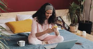 Happy african american girl chatting and text messaging on smartphone sitting on the bed at home. Young woman receives stock footage