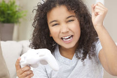Happy African American Girl Playing Video Games. Beautiful young happy mixed race interracial African American girl child celebrating playing video games Royalty Free Stock Photos