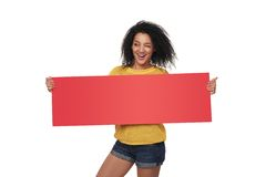 Happy african american girl showing blank banner. Happy playful mixed race african american - caucasian woman winking looking away, showing blank red banner Royalty Free Stock Images