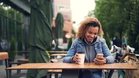 Happy African American girl is using smartphone touching screen and smiling while sitting in outdoor cafe in park. Happy African American girl is using stock footage