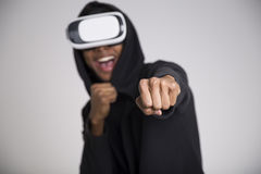 Happy African American guy playing vr game. Close up of an African American youth playing a virtual reality game and boxing. His fist is in the foreground. The Royalty Free Stock Images
