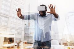 Happy African American having fun with virtual glasses. Enjoying life. Waist up of happy young African American wearing virtual glasses while standing in and Royalty Free Stock Photo