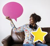 Happy African American holding copyspace speech bubble and a star sign stock photos