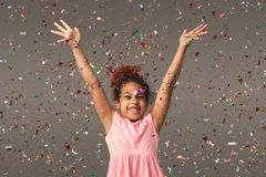 Happy black small girl at white studio background. Happy african-american little girl at gray studio background, copy space. Portrait of beautiful child having Royalty Free Stock Photo