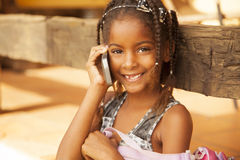 Happy african american little girl on the phone stock photography