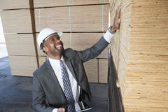 Happy African American male contractor inspecting wooden planks while holding tablet PC stock photo