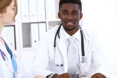Happy african american male doctor with medical staff at the hospital. Medicine concept. Happy african american male doctor with medical staff at the hospital Royalty Free Stock Images