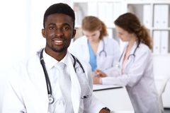 Happy african american male doctor with medical staff at the hospital. Medicine concept. Happy african american male doctor with medical staff at the hospital Stock Photo