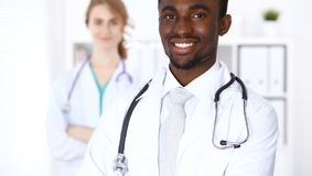Happy african american male doctor with medical staff at the hospital. Medicine concept. Happy african american male doctor with medical staff at the hospital Royalty Free Stock Photos
