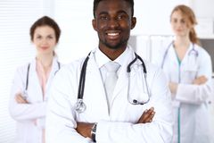 Happy african american male doctor with medical staff at the hospital. Medicine concept. Happy african american male doctor with medical staff at the hospital Royalty Free Stock Photo
