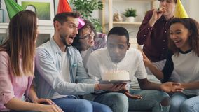 Happy African American man blowing candles on birthday cake laughing at home stock footage