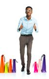 Happy african american man with fingers up and shopping bags on Stock Image