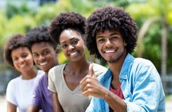 Happy african american man with group of young adults in line stock photography