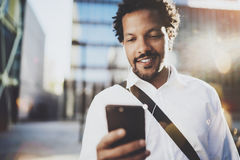 Happy African American man in headphone walking at sunny city and enjoying to listen to music on his smart phone.Blurred Stock Photos