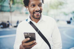 Happy African American man in headphone walking at sunny city and enjoying to music on his smartphone.Concept of guy Royalty Free Stock Images