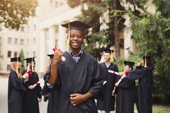 Happy african-american man on his graduation day. Young smiling african-american men on his graduation day in university, standing with multiethnic group of Stock Photo