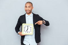 Happy african american man holding clock anf pointing on it. Happy african american young man holding clock anf pointing on it Stock Image