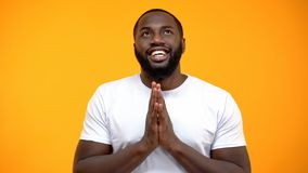 Happy African-American man holding hands for pray and looking up, blessing god. Stock photo stock photo