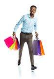 Happy african american man holding shopping bags on white backgr. Ound. Christmas and holidays concept Royalty Free Stock Photo