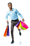 Happy african american man holding shopping bags on white backgr Stock Photos