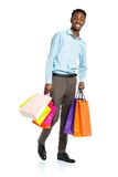 Happy african american man holding shopping bags on white backgr Royalty Free Stock Images