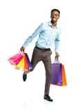 Happy african american man holding shopping bags on white backgr Royalty Free Stock Photo