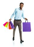 Happy african american man holding shopping bags on white backgr Stock Photography