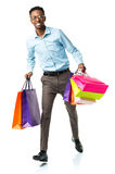 Happy african american man holding shopping bags on white backgr Stock Images