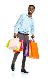 Happy african american man holding shopping bags on white  Royalty Free Stock Images