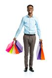 Happy african american man holding shopping bags on white  Stock Photography