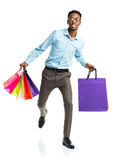 Happy african american man holding shopping bags on white. Holid Stock Photo