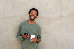 Happy african american man holding smart phone and coffee stock photography
