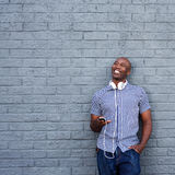 Happy african american man with a mobile phone and headphones Royalty Free Stock Image