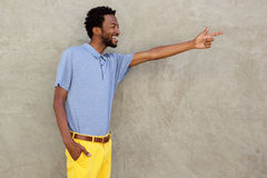 Happy african american man pointing to wall Stock Photography
