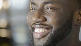 Happy African American man shining with healthy white smile, face close-up