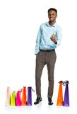 Happy african american man with shopping bags  and holding credi Royalty Free Stock Photo