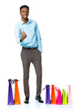 Happy african american man with shopping bags  and holding credi Stock Images