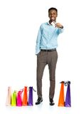 Happy african american man with shopping bags and holding credit Royalty Free Stock Photo
