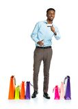 Happy african american man with shopping bags and holding credit Royalty Free Stock Photography