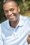 Happy African American Man Smiling. A happy African American man sitting outside and smiling with perfect white teeth Royalty Free Stock Photo